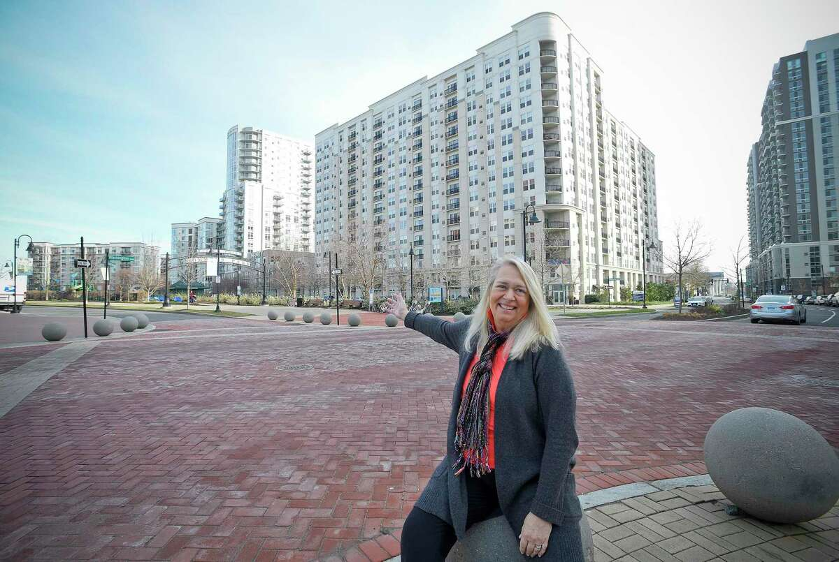 Infinity apartment building resident Terry Rogers gestures to the property, second from left, on Jan. 2, 2020. Rogers also owns the neighboring Harbor Point Wines & Spirits store at 130 Washington Blvd., in downtown Stamford, Conn.