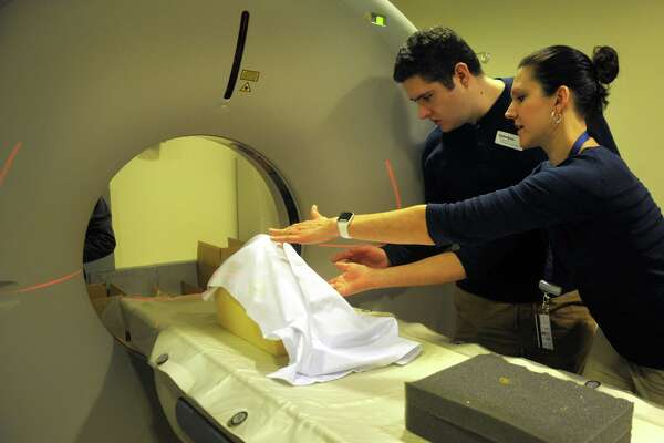Tania Grgurich, Clinical Associate Professor of Diagnostic Imagining, places a human skull, seen here covered by a cloth, into position in preparation of a CT Scan at Quinnipiac University's School of Health Science, in North Haven, Conn. Jan. 3, 2020. Quinnipiac is taking diagnostic imaging of the skeletal remains of three humans found recently buried during the renovation of an 18th century house in Ridgefield. Grgurich is seen here with radiological science student Zachary Gurahian, of Westport.