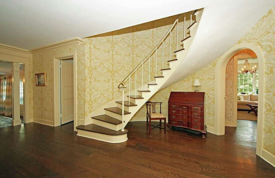 A gracefully curved floating staircase with a wrought iron and brass railing leads to the second floor from the center hall foyer.