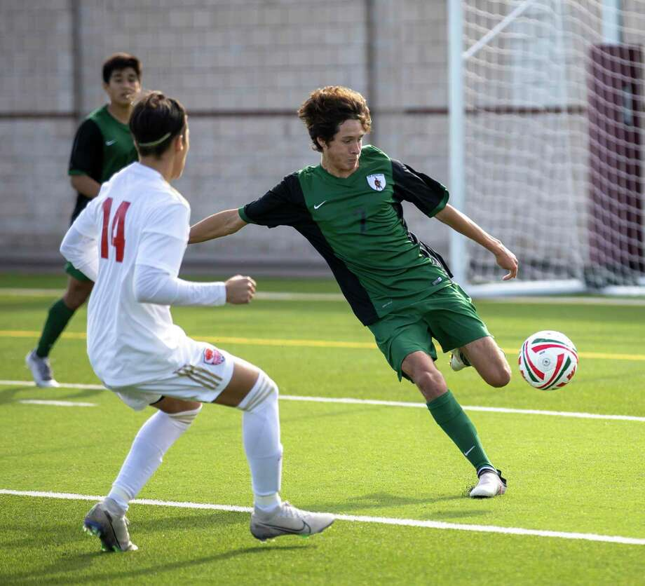 The Woodlands' Santi Balderas-Berg passes the ball under pressure from Caney Creek's Jorge Jaimes in a Kilt Cup tournament game at Woodforest Bank Stadium on Friday, Jan. 3, 2020. Photo: Gustavo Huerta, Houston Chronicle / Staff Photographer / Houston Chronicle