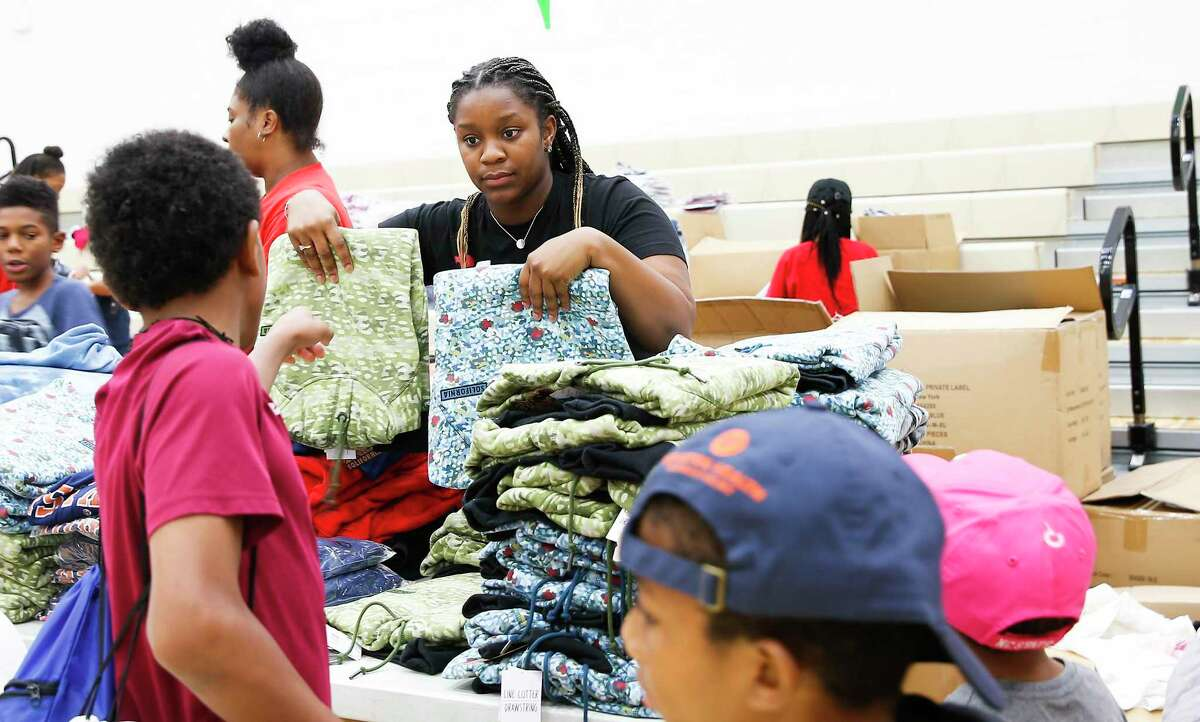 Volunteer Brianna Lewis holds up coats during Worthing High School hosts a