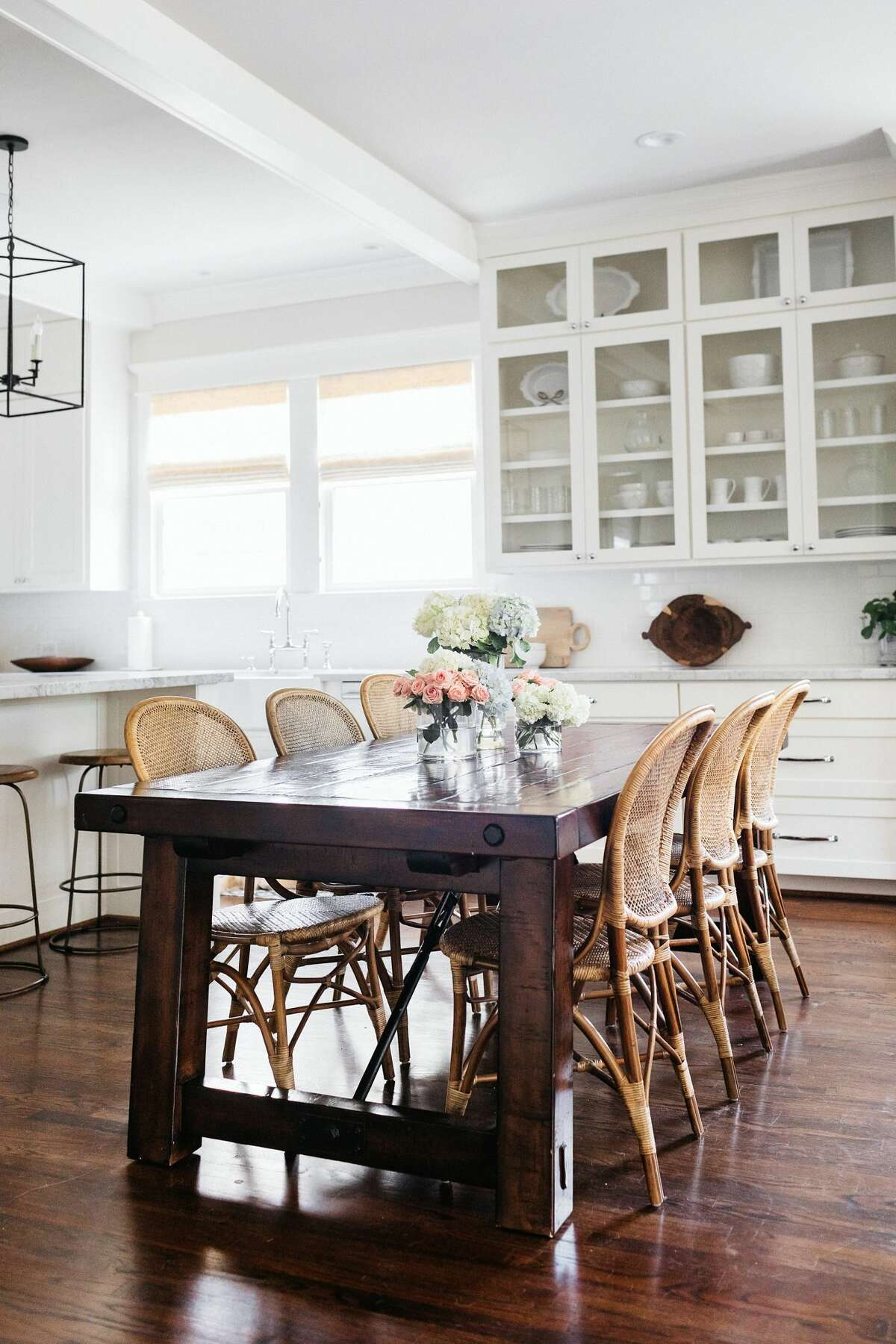 A wood table and rattan chairs add texture to the all-white kitchen.