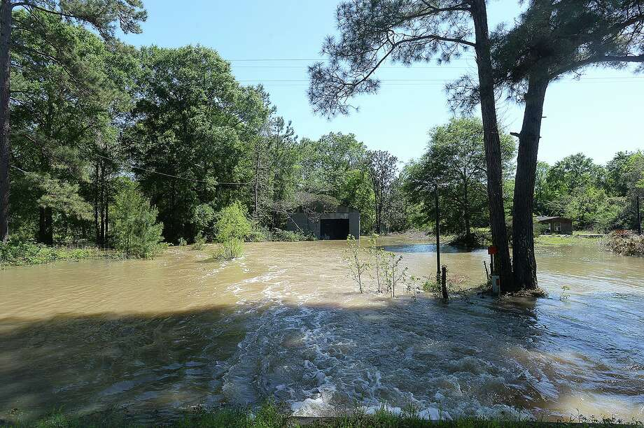 """Flood waters from a ditch running under FM 1416 in Newton County rush onto an abandoned property in Newton County Friday. Many residents of a Bon Wier neighborhood known as """"The Hole"""" evacuated Thursday as rising waters quickly flooded the area, nearing entry levels at some elevated homes. Heavy rainfall and the opening of the dams at Toledo Bend have swelled the Sabine River, area creeks and ditches and is expected to rise further through the weekend. Photo taken Friday, March 30, 2018 Kim Brent/The Enterprise Photo: Kim Brent / Kim Brent/Beaumont Enterprise / BEN"""
