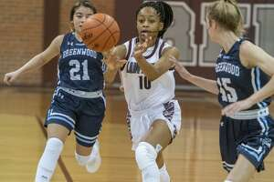 Lee's Destiny Stanford passes the ball after beating Greenwood's Natalia Lopez and Karsyn Payton press coverage 01/03/20 at the Lee High gym. Tim Fischer/Reporter-Telegram