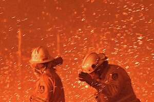 Australia has experienced weeks of wildfires. On Dec. 31, firefighters struggle against the strong wind in an effort to save nearby houses from fires near the town of Nowra in the Australian state of New South Wales.