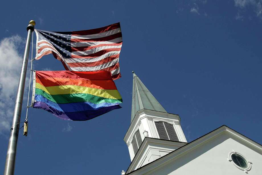 FILE - In this April 19, 2019, file photo, a gay pride rainbow flag flies along with the U.S. flag in front of the Asbury United Methodist Church in Prairie Village, Kan., United Methodist Church leaders are proposing creation of a separate division that would let more traditional denominations break away because of the disagreement with churches over the UMC's official stance on gay marriage. (AP Photo/Charlie Riedel, File) Photo: Charlie Riedel, STF / Associated Press / Copyright 2019 The Associated Press. All rights reserved.