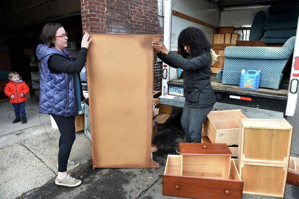 Bethany Delahunt, left, housing and donations coordinator for Integrated Refugee & Immigrant Services, and Liliane Toupou, housing and donations assistant, load a truck with furniture outside the IRIS warehouse in New Haven. Delahunt's son Oscar watches from nearby.