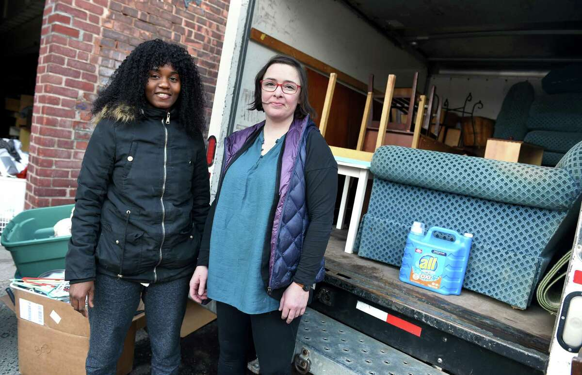 Liliane Toupou, left, housing and donations assistant for Integrated Refugee & Immigrant Services, and Bethany Delahunt, housing and donations coordinator, alongside a truck loaded with furniture outside an IRIS warehouse in New Haven.