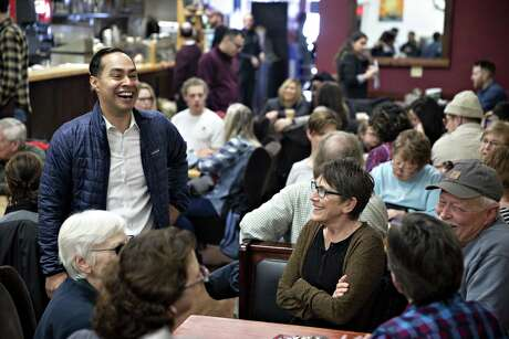 "Julian Castro, former secretary of Housing and Urban Development (HUD) and 2020 democratic presidential candidate, left, greets attendees during a campaign stop at the Better Day Cafe in Storm Lake, Iowa, U.S., on Saturday, Feb. 23, 2019. Castro, who hopes to become the first Latino president, has stated that he believes President Donald Trump ""has tried to harness"" racial tensions for political gain. Photographer: Daniel Acker/Bloomberg"