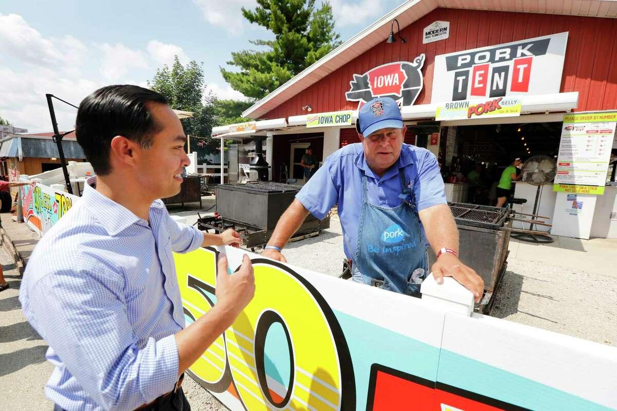 Former San Antonio Mayor Julián Castro talks with Iowa Pork Producers tent worker Dana Wanken during a visit to the Iowa State Fair.