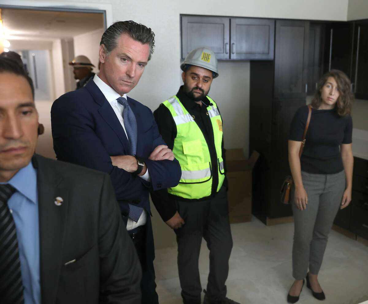 Governor Gavin Newsom (left), JHF project manager Kyan Hakimi (middle), and Emeryville mayor Ally Medina (right) take a look at a kitchen and apartment at Estrella Vista Apartments, a new affordable housing development under construction on Tuesday, July 2, 2019, in Emeryville, Calif.