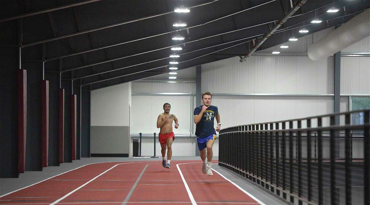 Ryan Escoda, of Newtown, right, and Christopher Fernandes, of Bethel, run on the new track in the new Track & Field Training Center at Bethel High School on Friday. Escoda and Fernandes are both on the track team at Eastern Connecticut State University.