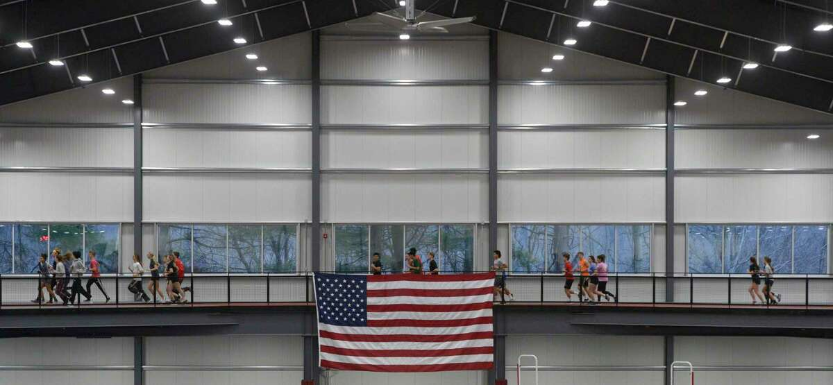 The track team warms up before practice in the new Track & Field Training Center at Bethel High School. The center was build thanks to a donor and will provide space for athletes and students to practice. Friday, January 3, 2020, in Bethel, Conn.