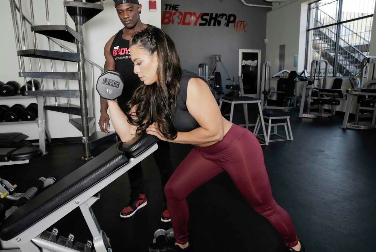"""Cintia Guerra demonstrates biceps curls as her trainer Ian Buchanan, watches. """"Progress over perfection is the biggest thing,"""" according to Buchanan."""