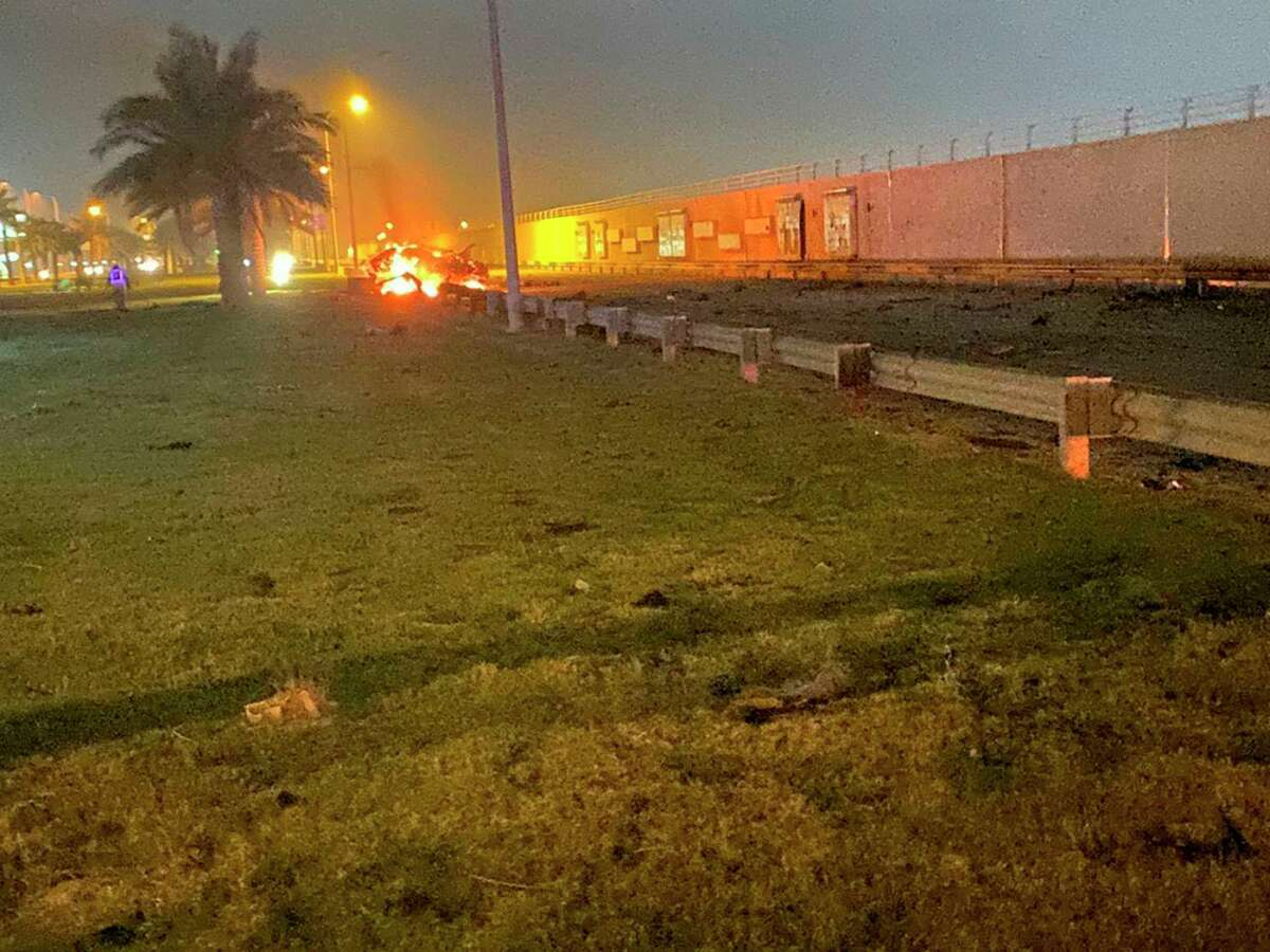 This photo released by the Iraqi Prime Minister Press Office shows a burning vehicle at the Baghdad International Airport following an airstrike, in Baghdad, Iraq, early Friday. Oil prices jumped