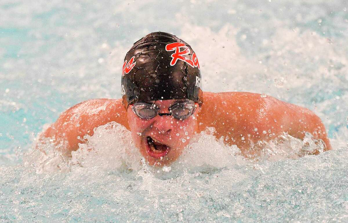 New Canaan's Michael Rivas competes in the boys 100-meter butterfly during a dual swim/dive meet at the New Canaan YMCA Valles Natatorium on Friday in New Canaan.