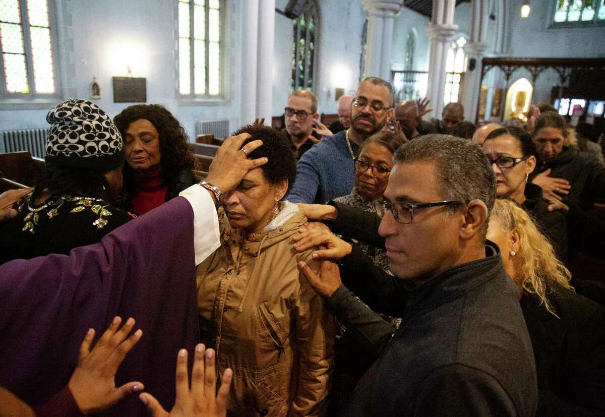 The Rev. Luis Barrios, left, places his hand on the head of Mercedes Katrocino, center, a deaf congregant, as he and the rest of the congregation pray for Katrocino's health and failing eyesight at Holyrood Episcopal Church in the Washington Heights neighborhood in New York City, Sunday, Dec. 15, 2019. (AP Photo/Jessie Wardarksi)