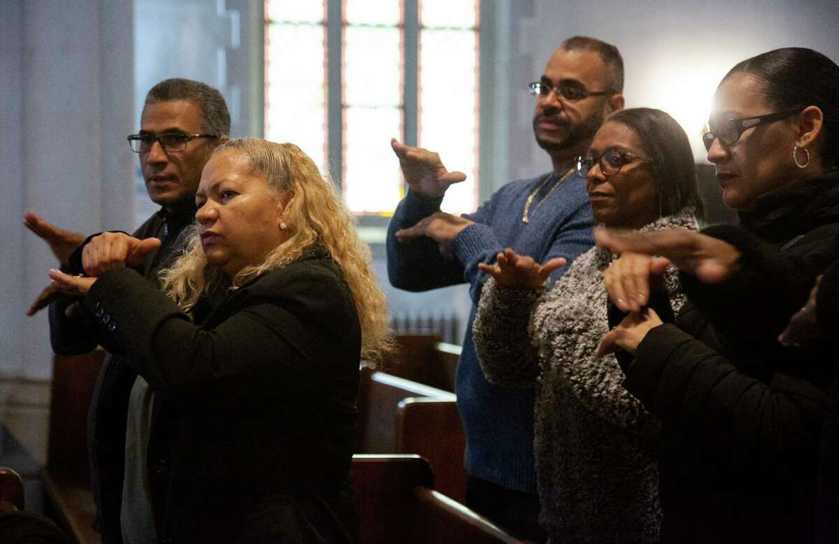 Worshippers Carlos Tirado, left, and Lidia Martinez, second from left, sign in response to a sermon at Holyrood Episcopal Church-Iglesia Santa Cruz in the Washington Heights neighborhood in New York City, Sunday, Dec. 22, 2019. Tirado and Martinez, who are deaf, began attending the church last year after seeing the Rev. Maria Santiviago give sermons in sign language. (AP Photo/Jessie Wardarksi)