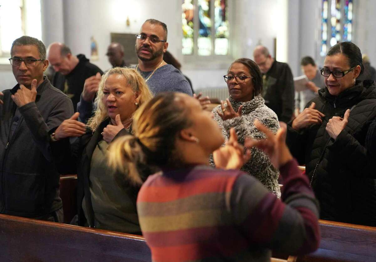 In a Sunday, Dec. 15, 2019 photo, deaf worshippers sign a hymn while following sign language interpreter Diely Martinez at Holyrood Episcopal Church-Iglesia Santa Cruz in New York City. (AP Photo/Emily Leshner)
