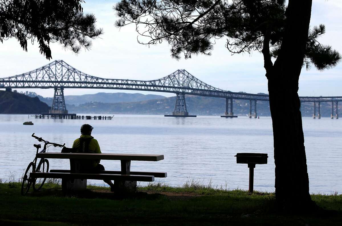 Bicyclist David Bullen takes in the view of the Richmond-San Rafael Bridge from Point Molate Beach Park in Richmond, Calif. before his ride back to Albany on Tuesday, Dec. 31, 2019. State assemblyman Marc Levine is urging Caltrans consider rebuilding the aging span that links Marin and Contra Costa counties.