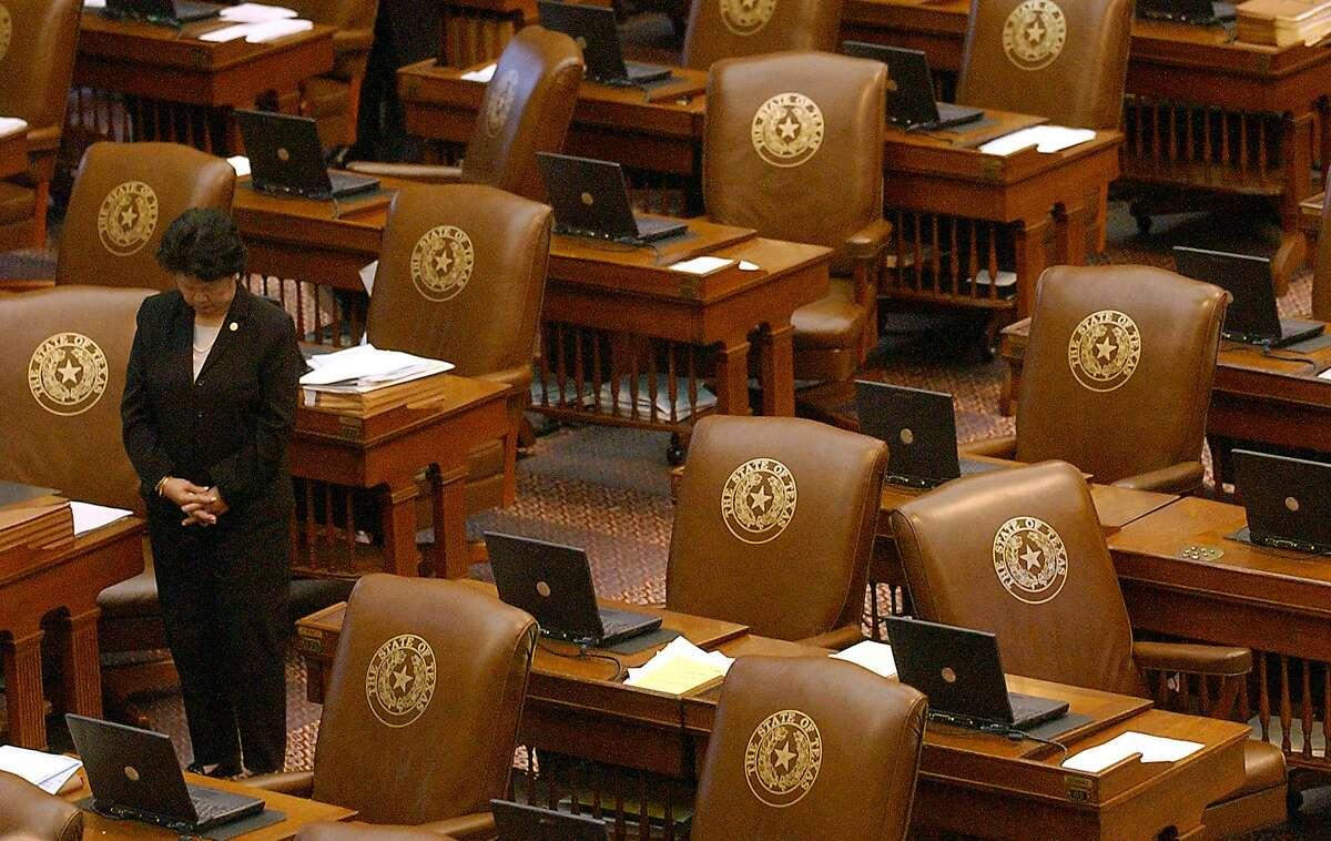 File photo shows Rep. Martha Wong, R-Houston, bowing her head during the invocation surrounded by empty desks on the House floor of the Capitol in Austin Monday, May 12, 2003. More than 50 Democrats, enough to break the quorum needed to do Texas House business, did not show up Monday morning when the House convened, prompting Republican Speaker Tom Craddick to order state police officers to find them. The walkout, which coincided with the scheduled debate for a divisive congressional redistricting bill, halted House business.