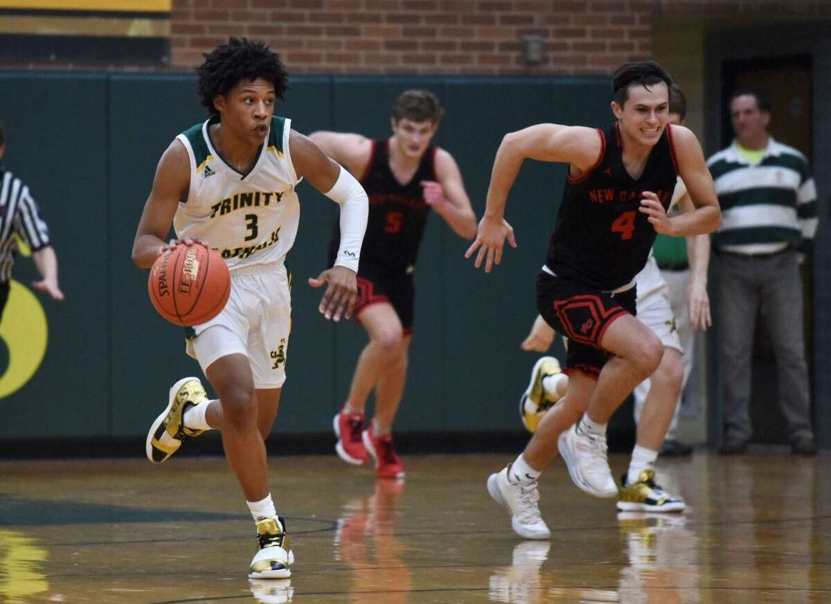 Trinity Catholic's Andrew Saint-Louis (3) breaks out with New Canaan's Brandon Sechan (4) and Alex Gibbens (5) in pursuit during a boys basketball game on Friday in Stamford.