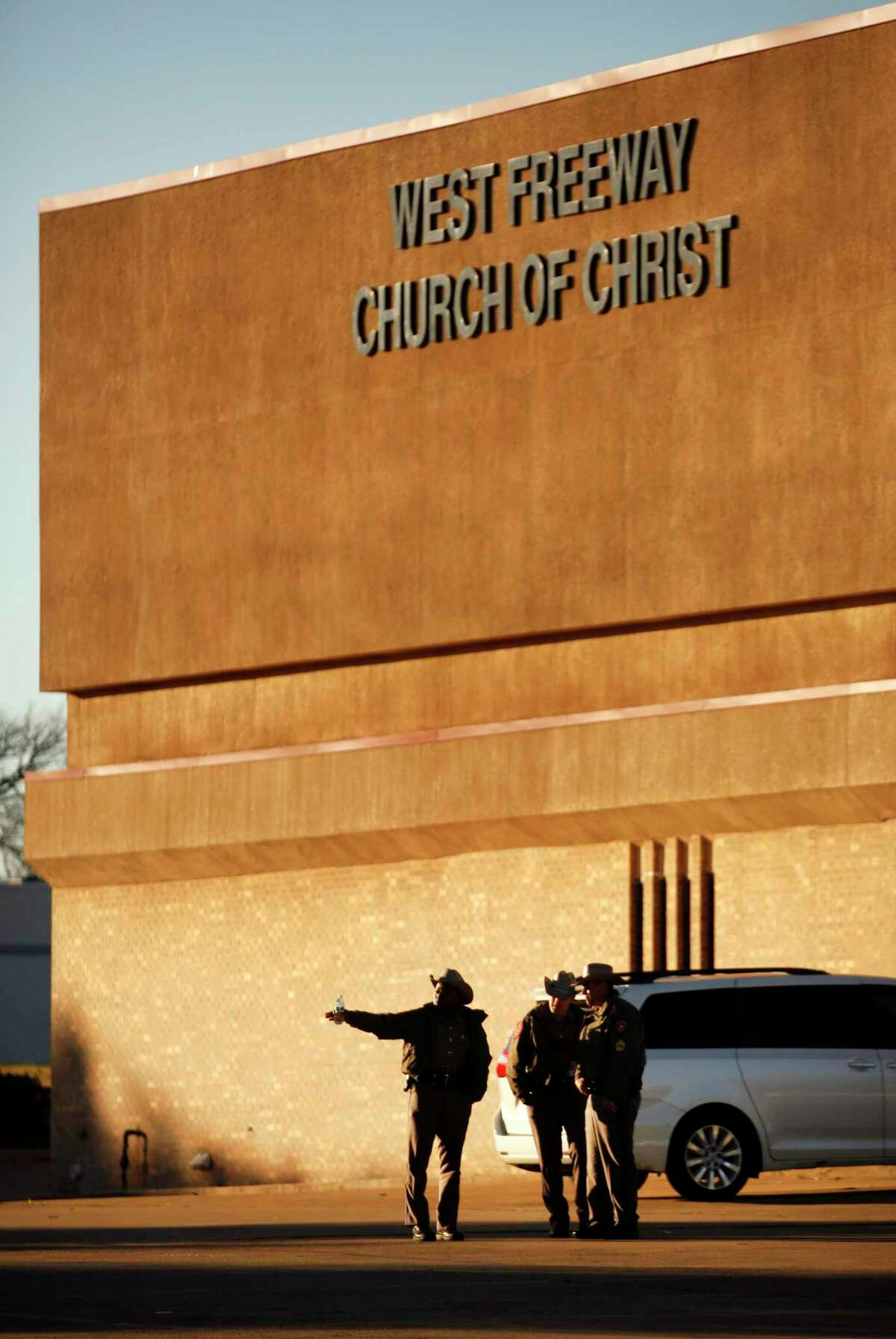 Texas Department of Public Safety troopers secure the parking lot before church and community members gather outside the West Freeway Church of Christ for a candlelight vigil, Monday, Dec. 30, 2019, in White Settlement, Texas. A gunman shot and killed two people before an armed security officer returned fire, killing him during a service at the church on Sunday.
