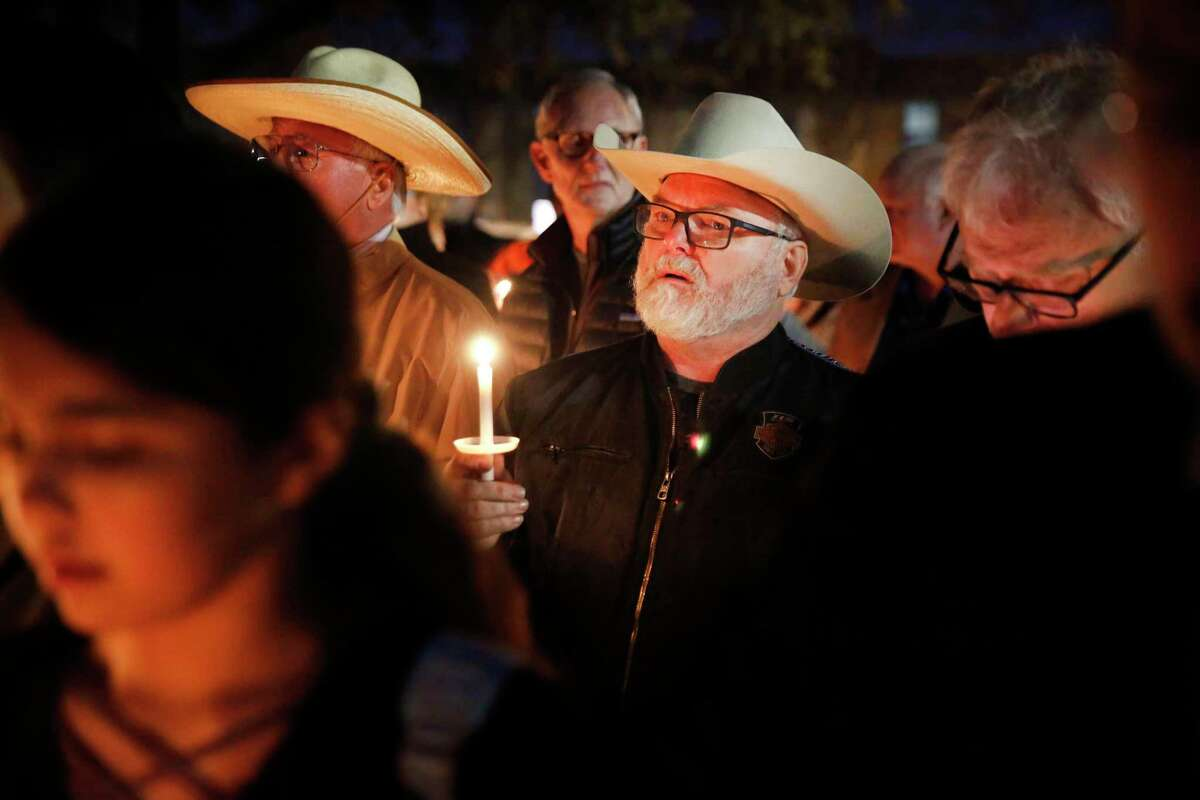 Stephen Willeford, center, who confronted and exchanged gunfire with the Sutherland Springs church shooter in 2017, joins church and community members gathered outside West Freeway Church of Christ for a candlelight vigil, Monday, Dec. 30, 2019, in White Settlement, Texas. A gunman shot and killed two people before an armed security officer returned fire, killing him during a service at the church on Sunday.