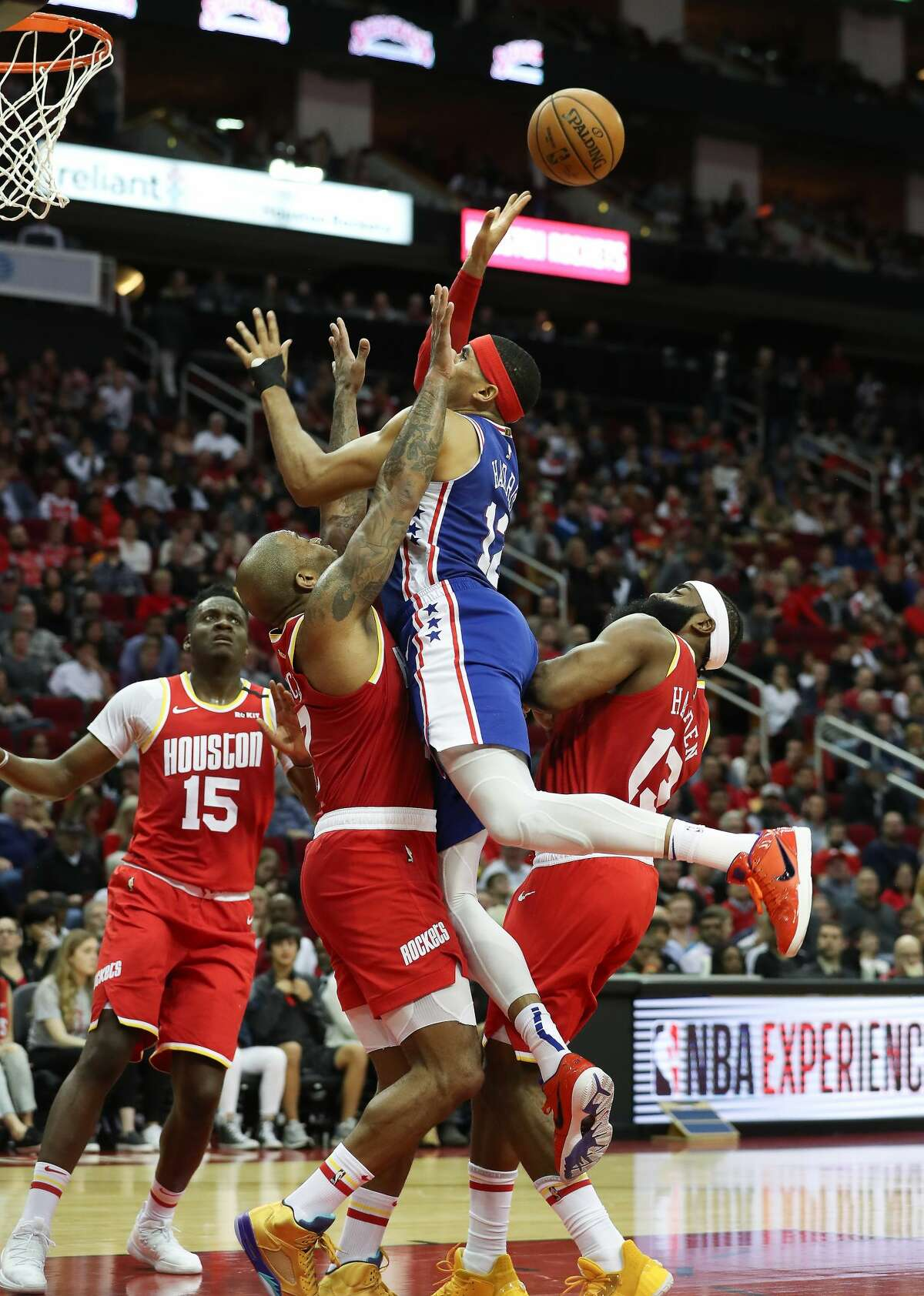 Philadelphia 76ers forward Mike Scott (12) attempts to score under pressure from Houston Rockets defenders during the first half of an NBA basketball game at Toyota Center on Friday, Jan. 3, 2020, in Houston.