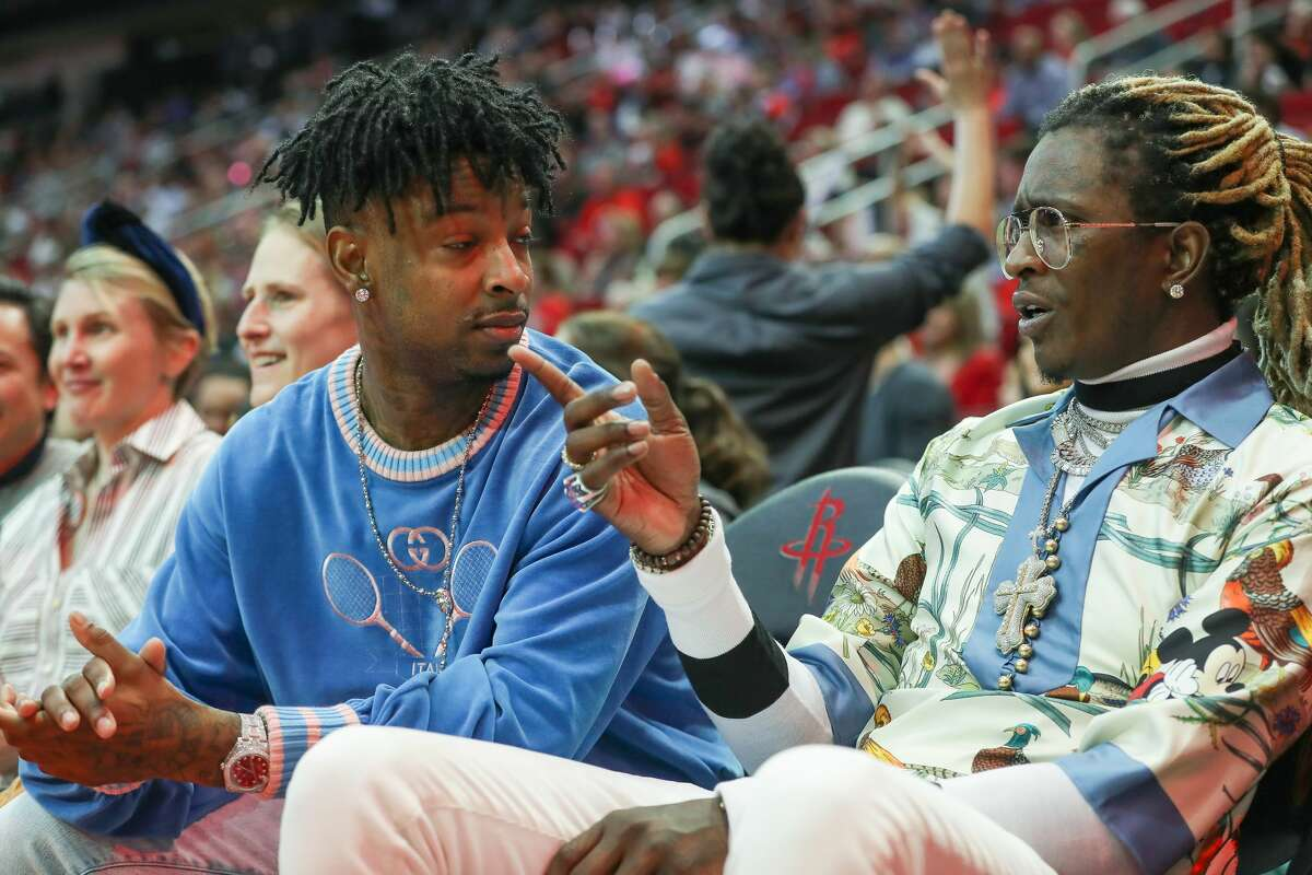 Rappers 21 Savage (left) and Young Thug sit courtside during the Houston Rockets NBA basketball game at Toyota Center on Friday, Jan. 3, 2020, in Houston.