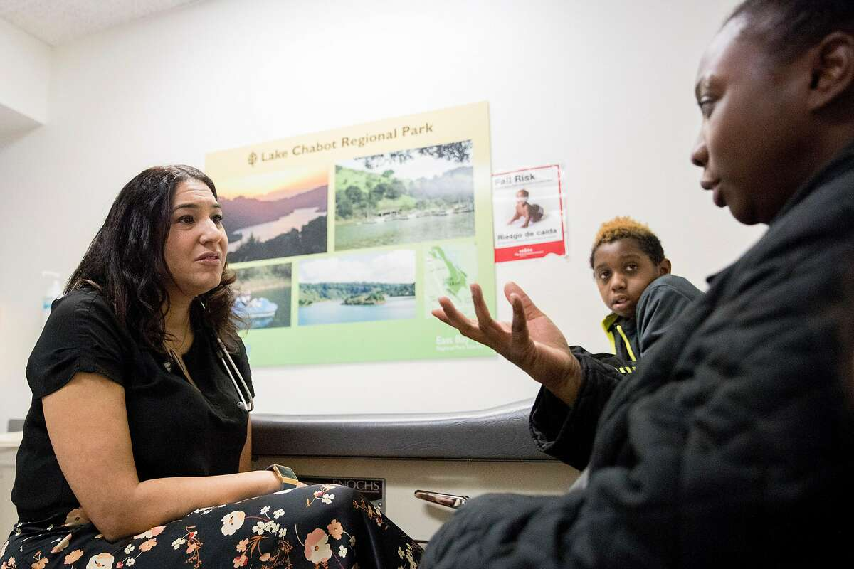 Dr. Dayna Long (left) meets with Tanisha Hopkins of Berkeley (right) and her son, Angelo Bostic, 10, to discuss new screening tools she's developing while at UCSF Benioff Children's Hospital Claremont Clinic East in Oakland , Calif. Friday, Jan. 3, 2020.