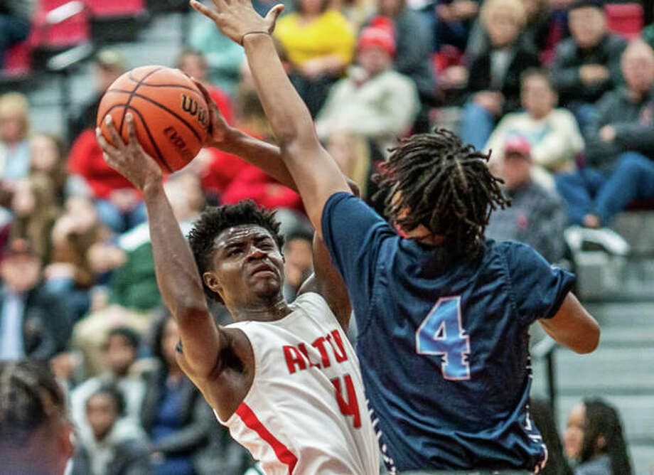 Alton's Ky'lun Rivers, left, puts up a shot while being guarded by Marlon Stacker of Belleville East in Friday night's Southwestern Conference game at Alton High School. Rivers scored nine points in the game, but Alton lost 70-61. Photo: Nathan Woodside | The Telegraph