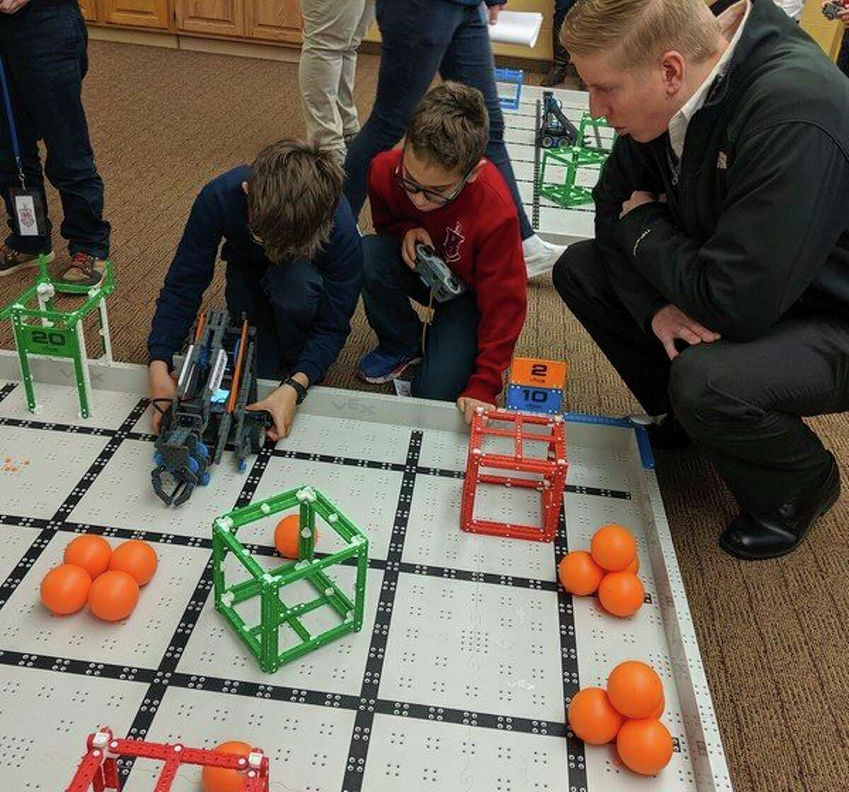Two Manistee Catholic Central students line up their robot to take a test run on a track at a recent showing of their work at the school. The Sabers are hoping to qualify someone for the state competition this year. (Courtesy photo)