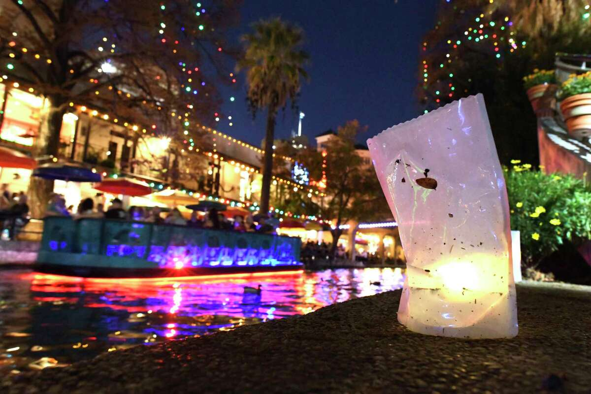 A barge on the San Antonio River along the River Walk cruises by a luminaria during the Fiesta de las Luminarias on the River Walk on Saturday, Dec. 1, 2018.
