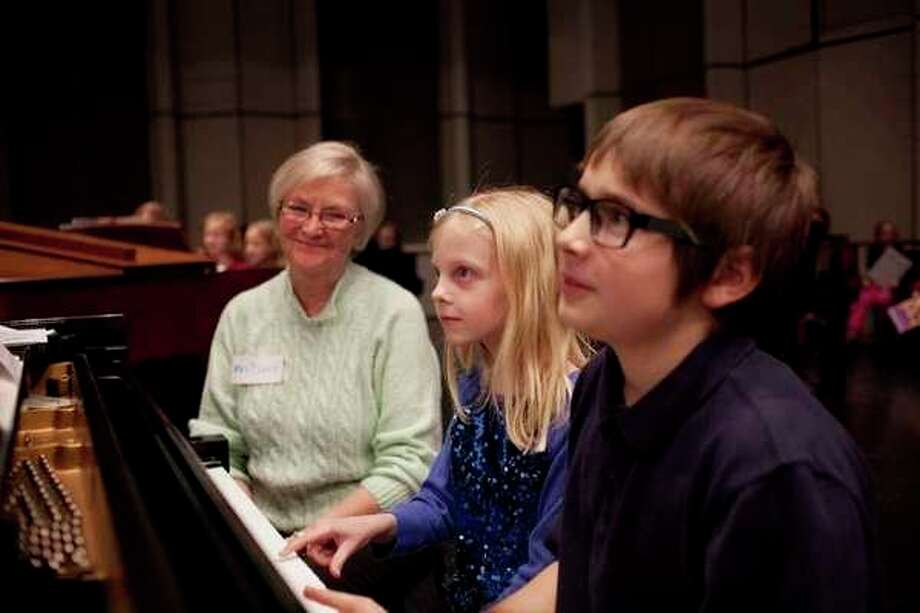 Madeline Arthur, 8, and Kevin Everson, 9, practice playing the last note of their song as piano teacher Elizabeth Dianis watches during a 2015 rehearsal for KeyboardFest at the Midland Center for the Arts. (Daily News file photo)