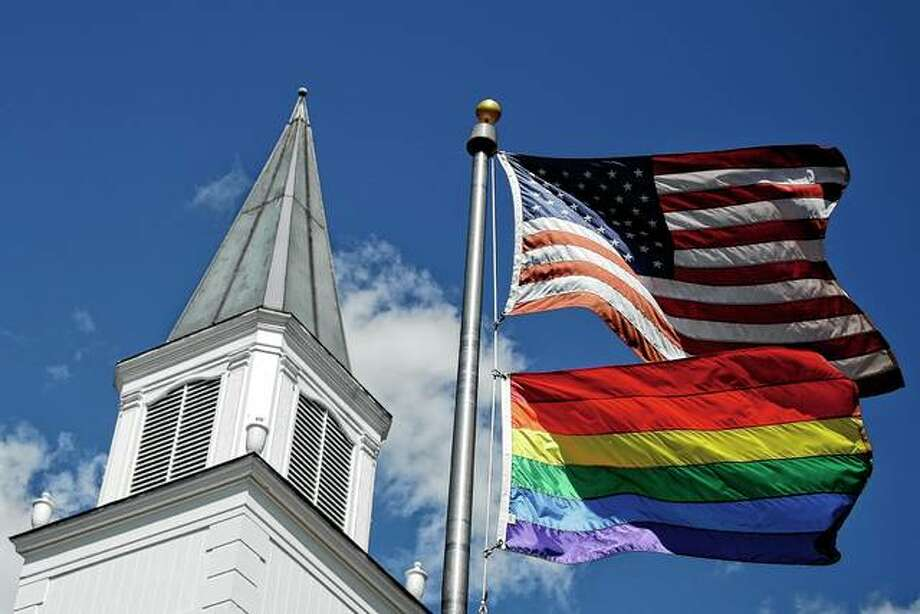 A gay pride rainbow flag flies along with the U.S. flag in April in front of Asbury United Methodist Church in Prairie Village, Kansas. United Methodist Church leaders are proposing a separation that would let more traditional denominations break away because of a disagreement over the UMC's official stance on gay marriage. Photo: Charlie Riedel | Associated Press