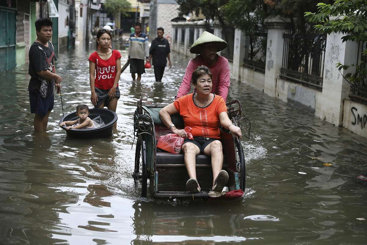 A woman rides a tricycle on a flooded street in Jakarta, Indonesia, Saturday, Jan. 4, 2020. Monsoon rains and rising rivers submerged parts of greater Jakarta and caused landslides in Bogor and Depok districts on the city's outskirts as well as in neighboring Lebak, which buried a number of people. (AP Photo/Dita Alangkara)
