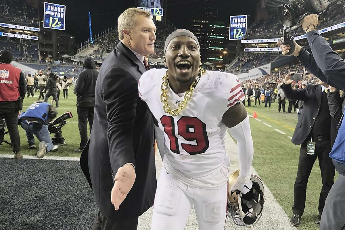 San Francisco 49ers wide receiver Deebo Samuel (19) races past general manager John Lynch after the team beat the Seattle Seahawks in an NFL football game, Sunday, Dec. 29, 2019, in Seattle. (AP Photo/Stephen Brashear)