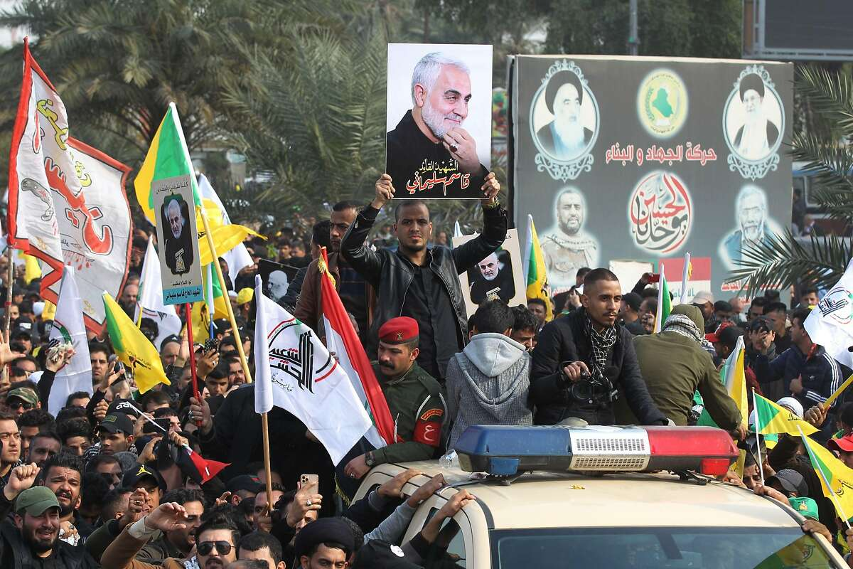 """Mourners surround a car carrying the coffin of Iranian military commander Qasem Soleimani during a funeral procession, for him and nine others, in Baghdad's district of al-Jadriya, near the high-security Green Zone, on January 4, 2020. - Thousands of Iraqis chanting """"Death to America"""" joined the funeral procession for Soleimani and Iraqi paramilitary chief Abu Mahdi al-Muhandis, both killed in a US air strike. The cortege set off around Kadhimiya, a Shiite pilgrimage district of Baghdad, before heading to the Green Zone government and diplomatic district where a state funeral was to be held attended by top dignitaries. In all, 10 people -- five Iraqis and five Iranians -- were killed in Friday morning's US strike on their motorcade just outside Baghdad airport. (Photo by AHMAD AL-RUBAYE / AFP) (Photo by AHMAD AL-RUBAYE/AFP via Getty Images)"""