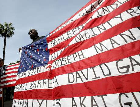 FILE — In this April 8, 2019 file photo, Malaki Seku Amen holds up an American flag with the names of people shot and killed by law enforcement officers, as he and others in rally in support of a bill that would restrict the use of deadly force by police, in Sacramento, Calif. The shooting death of Stephon Clark by Sacramento Police, helped spur the passage of two laws to take effect in 2020 giving California one of the nation's most comprehensive approaches to deterring shootings by police. One changes the legal standard for when police can use deadly force, while the companion law increased officers' training on how to handle confrontations. (AP Photo/Rich Pedroncelli, File)