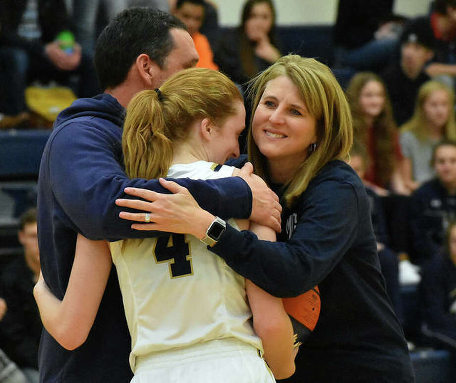 Father McGivney guard Anna McKee, center, is congratulated by her parents following Saturday's win. She scored 14 points to surpass 1,000 points for her career. Photo: Matt Kamp|The Intelligencer