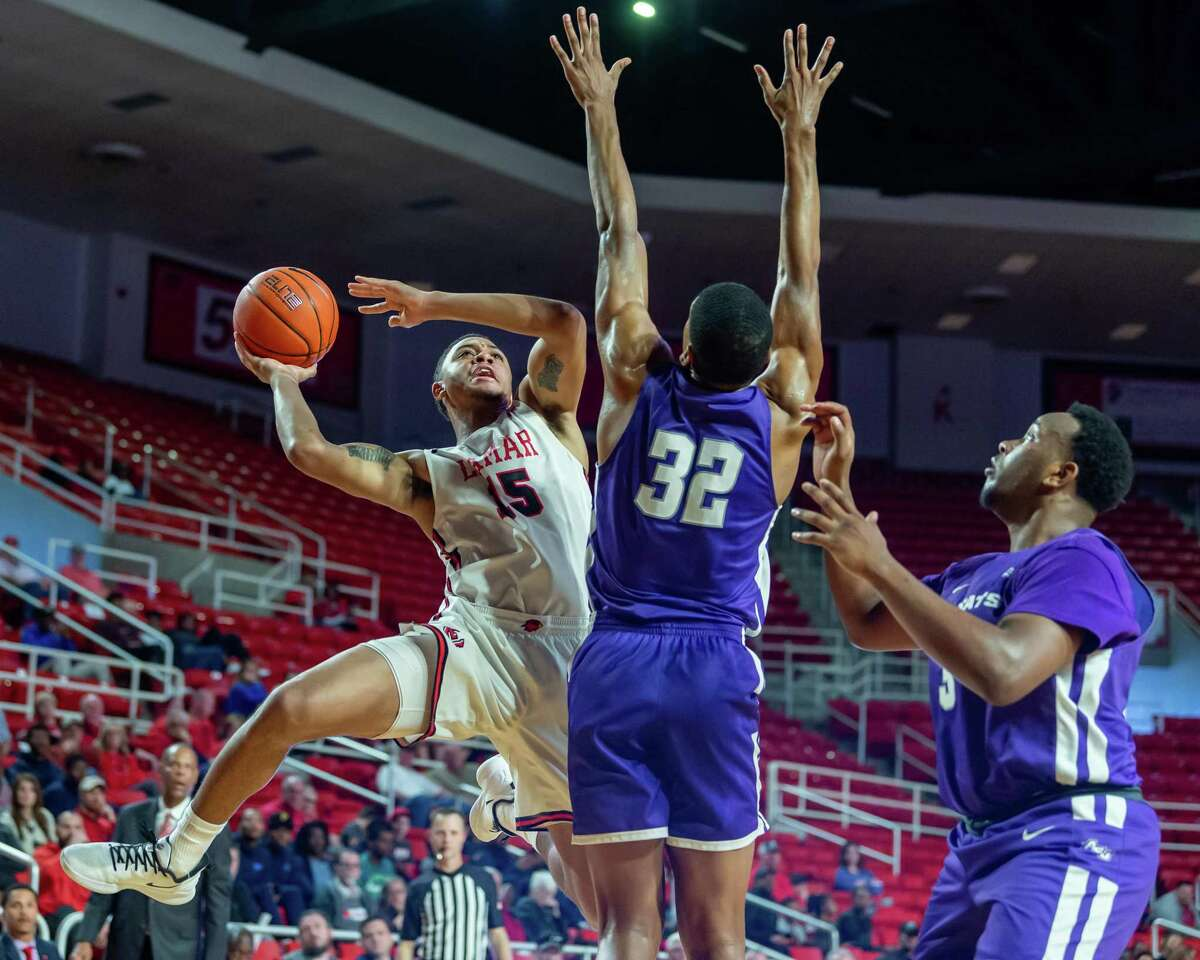 T.J. Atwood (15) puts up a shot around Joe Pleasant (32) as the Lamar Cardinals were in a hard-fought battle in their game with the Wildcats of Abilene Christian at the Montagne Center on Saturday, January 4, 2020. Fran Ruchalski/The Enterprise