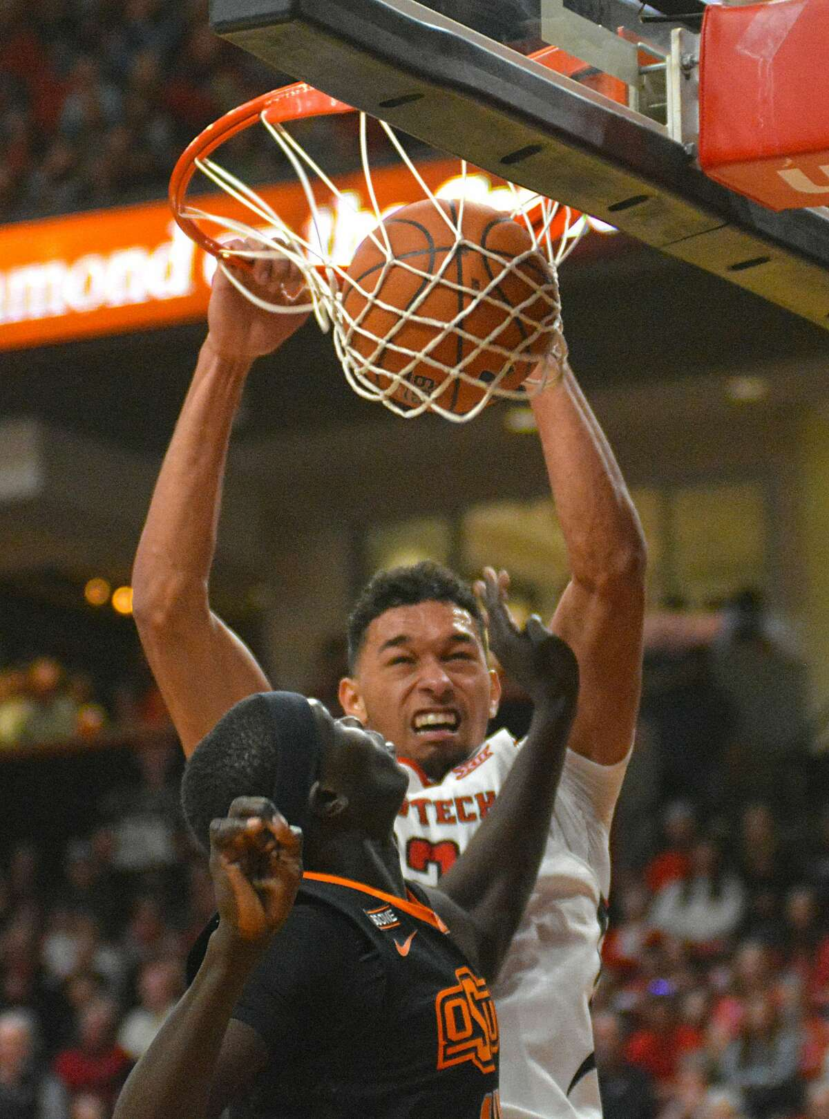 Texas Tech's T.J. Holyfield slams in a dunk over Oklahoma State defender Yor Anei during their Big 12 men's basketball game on Saturday in the United Supermarkets Arena.