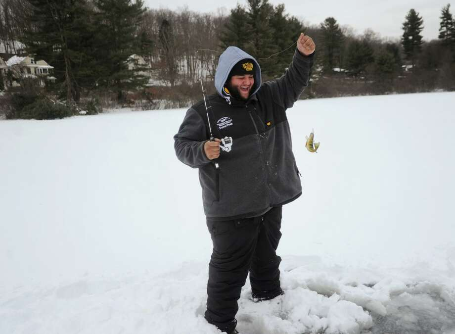 File photo: Danny Paez, of Stratford, celebrates catching a yellow perch from beneath the ice during an afternoon of ice fishing on Quillinan Reservoir in Ansonia, Conn. Taken on Monday, January 8, 2018. Photo: Brian A. Pounds / Hearst Connecticut Media / Connecticut Post