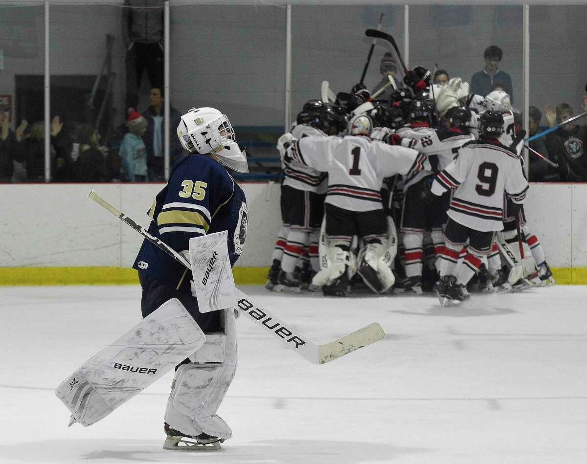 Notre Dame-Fairfield goalie Reagin Gallagher (35) skates off as New Canaan celebrates their over-time winning goal by Sam Augustine (26) in a boys hockey game at the Darien Ice House on Jan. 4, 2020 in Darien, Connecticut. New Canaan won 3-2 in over-time.