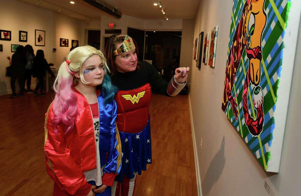 Isobel Roche and her mother Laura Roche enjoy works by Al Sarkis Munro during The ?Rene Soto Gallery Comics & Animation Art Show opening reception Saturday, January 4, 2020, at the gallery on Wall Street in Norwalk, Conn. Artists Al Sarkis Munro and Heather Gil & Naty were featured in the show that was curated by Alexandra McDaniel. Guests at the opening were encouraged to dress up as their favorite comic book characters.