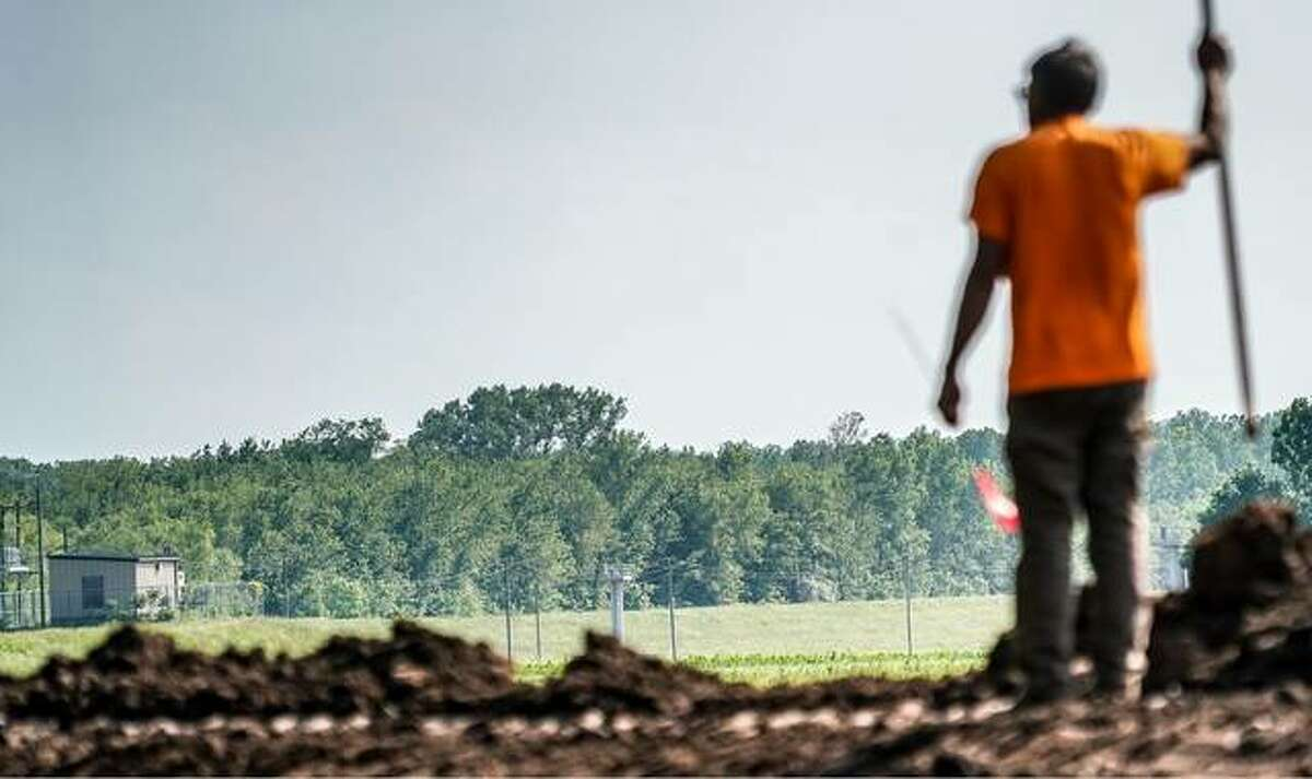 A volunteer stands on top of a makeshift secondary levee built from dirt to protect the village of Nutwood in Calhoun County, as he looks out toward the Nutwood Levee a couple days before it breached during flooding in 2019.