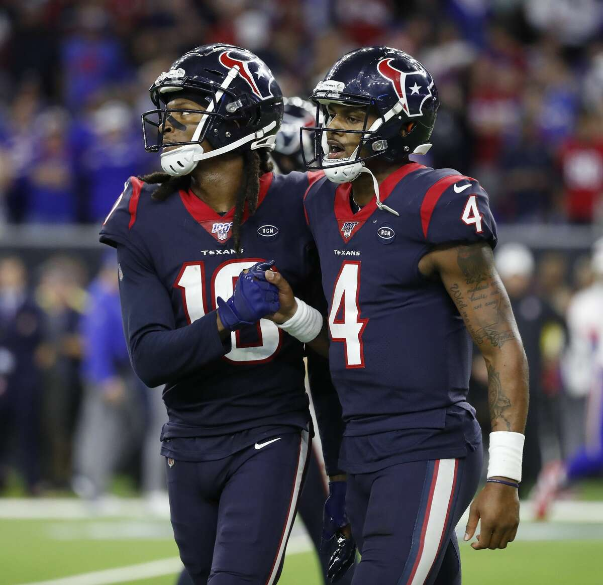 Houston Texans quarterback Deshaun Watson (4) celebrates with wide receiver DeAndre Hopkins (10) after connecting with Texans running back Taiwan Jones (34) which set up the game winning field goal during overtime of an AFC NFL wild card playoff game at NRG Stadium, Saturday, Jan. 4, 2020, in Houston.