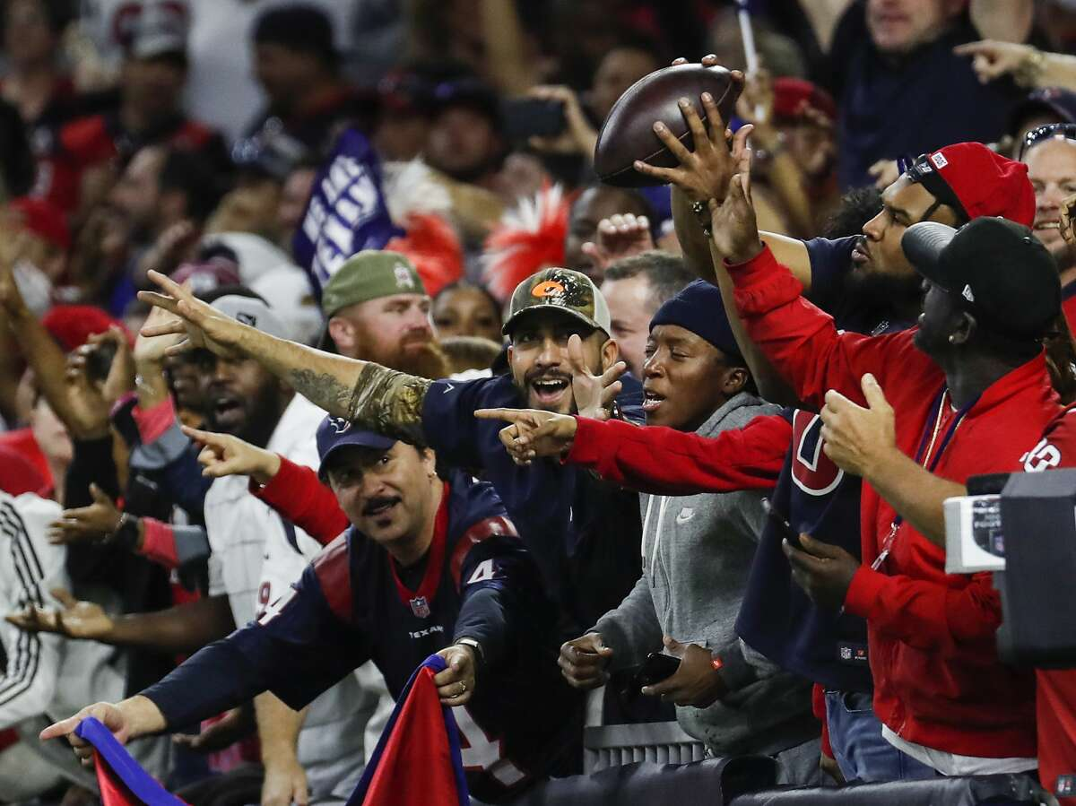 Houston Texans fans catch a ball tossed into the stands by Houston Texans wide receiver DeAndre Hopkins after he scored on a 2-point conversion during the fourth quarter of an AFC wild card playoff game at NRG Stadium on Saturday, Jan. 4, 2020, in Houston.