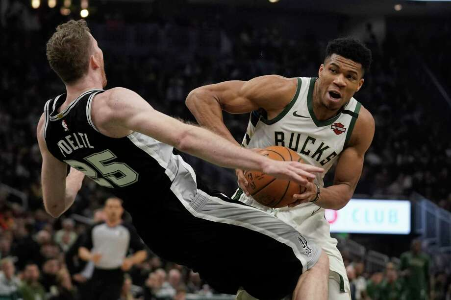 Jakob Poeltl fouls Milwaukee's Giannis Antetokounmpo, who got off to a slow start with just nine first-half points. Photo: Morry Gash /Associated Press / Copyright 2020 The Associated Press. All rights reserved.